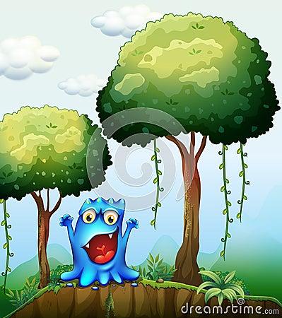Een het glimlachen blauw monster bij het bos dichtbij de klip