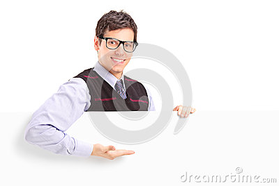 Een het glimlachen knappe kerel die op een wit paneel gesturing