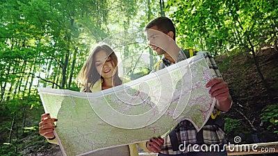 Een jong paar van toeristen die een kaart bekijken Zij bevinden zich in de stralen van de zon in het bos dichtbij de waterval stock video