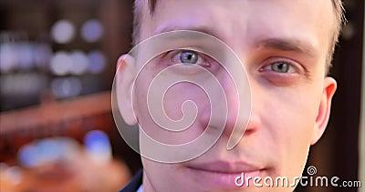 Een jonge beambte Een mens in een grijze kostuumgangen langs een venster in een duur bureau, onderzoekt de camera, glimlacht stock video