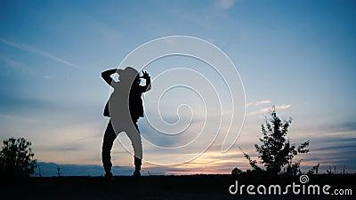 Een jonge mensen dansende disco bij zonsondergang, zijn silhouet is zichtbare, langzame motie stock videobeelden