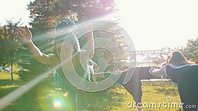 Een jonge vrouw met blauwe dreadlocks die zich op één been bevinden en houdt buiten het saldo - yoga stock video