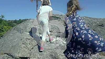 Een jonge vrouw met haar twee dochters beklimt een rots boven het overzees stock footage