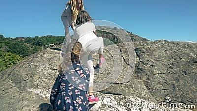 Een jonge vrouw met haar twee dochters beklimt een rots boven het overzees stock video