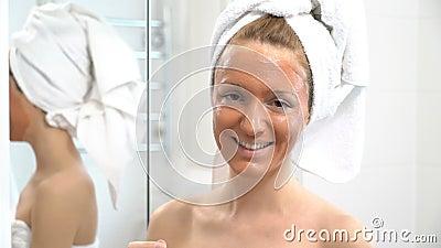 Een jonge vrouw met een witte handdoek zette op haar gezicht bruine bevochtigende mas stock footage