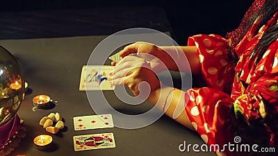 Een jonge zigeuner in een rode kleding bij een lijst door kaarslicht leest de toekomst met het fortunetelling van kaarten stock video