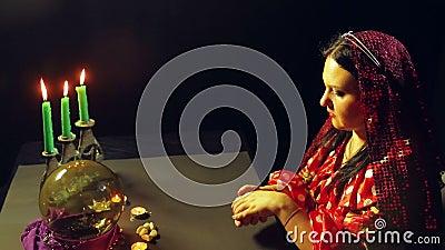 Een jonge zigeuner in een rode kleding bij een lijst door kaarslicht leest de toekomst met het fortunetelling van kaarten Het gem stock video