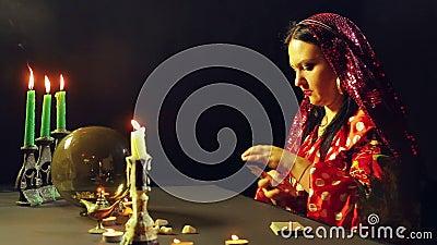 Een jonge zigeuner in een rode kleding bij een lijst door kaarslicht leest de toekomst met het fortunetelling van kaarten Het gem stock footage