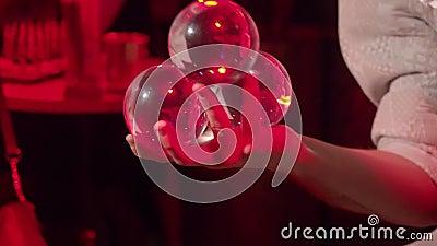 Een jongeman oefent verbluffende contacten met transparante ballen in rood licht Een partij Sluiten stock videobeelden
