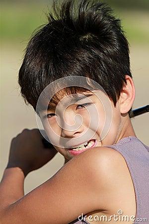 Een jongen 10 plaatst - omhoog om een golfbal bij het strand te raken