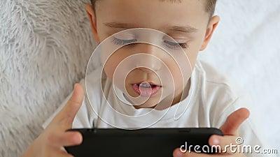Een kind houdt een smartphone voor hem en speelt spelen in langzame motie op een witte achtergrond stock footage