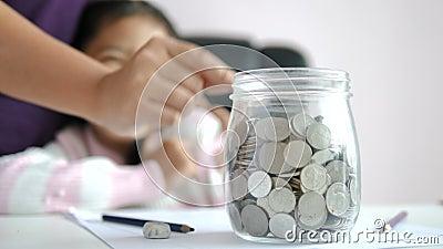 Een klein Aziatisch meisje gooide de munt in de spaarpot en glimlachte met geluk om geld te besparen op de rijkdom in de toekomst stock videobeelden