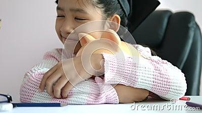 Een klein Aziatisch meisje gooide de munt in de spaarpot en glimlachte met geluk om geld te besparen op de rijkdom in de toekomst stock video