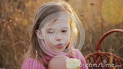 Een klein meisje die een appel eten bij een picknick stock video video 64073755 - Klein meisje idee ...