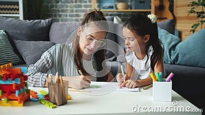 Een klein meisje met een creatieve tekening van een kind maken terwijl moeder haar liefde helpt uiten stock video