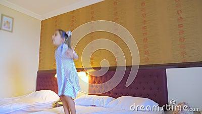 Een klein meisje springt in bed in een hotelkamer, heeft plezier en geniet van het leven stock video