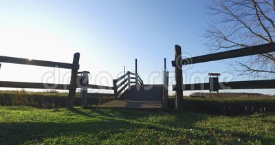 Een kleine houten brug over het kanaal, een momentopname van de omgeving met blauwe lucht op de achtergrond stock video
