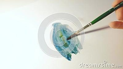 Een kleurenpalet met kleuren en een vrouwenhand die een abstracte tekening met een penseel tekent stock video