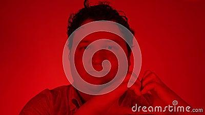 Een knappe man die een hartgebaar maakt met zijn vingers om zijn liefde en genegenheid te tonen, rood licht stock videobeelden