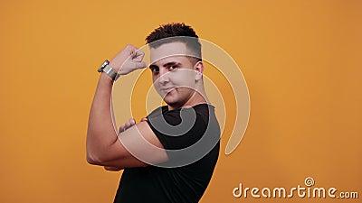 Een knappe man die naar camera kijkt, spieren toont, mooie klok heeft stock videobeelden
