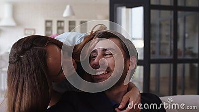 Een lachende vrouw die van achter in appartement naar man komt Man die haar omhelst stock videobeelden