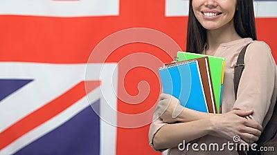 Een lachende vrouw met copybooks die tegen de Britse vlag staat, onderwijs in Groot-Brittannië stock footage