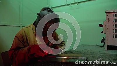 Een lasser voert het lassen van twee metaaldelen van uit de elektrode In hand vliegvonken stock videobeelden