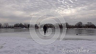 Een man die zwart op ijs loopt stock videobeelden