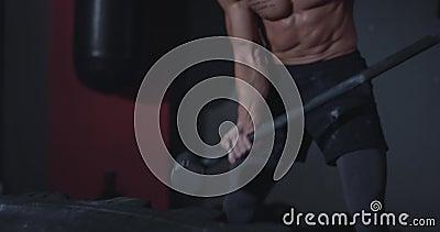 Een man met een geschikt lichaam en vol krachtstaven met een hummer over een grote band in een fitnessklasse stock footage