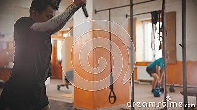 Een man met een zwart T-shirt die een grote band raakt met een metalen hamer in de gymzaal - een andere man die met zijn gewicht  stock videobeelden