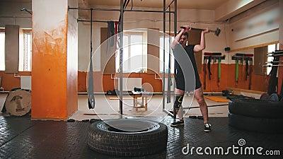 Een man met een zwart T-shirt die een grote band raakt met een metalen hamer in de gymzaal stock video