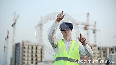 Een man in virtuele reality bril helm en vest op de achtergrond van de bouw controleert de handen van de interface stock video