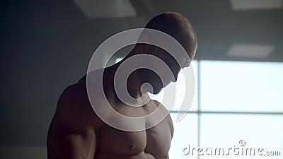 Een man zonder T-shirt wacht en past zich aan de oefening aan Verwachting Klaar voor het uitvoeren van een beslissende oefening a stock video