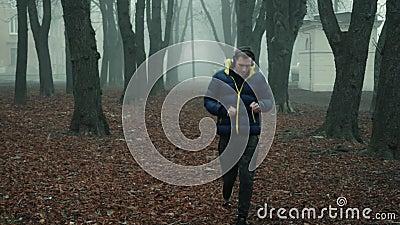 Een mannelijke atleet rijdt in een stadspark op een koude ochtend in de mist en haalt zijn draadloze hoofdtelefoon uit stock footage