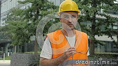 Een mannelijke industrieel ingenieur in een harde hoed en een veiligheidslak die langs moderne gebouwen loopt en met camera praat stock videobeelden
