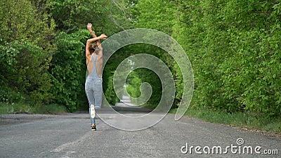 Een meisje in jeans loopt globaal langs de weg, langzame motie stock footage