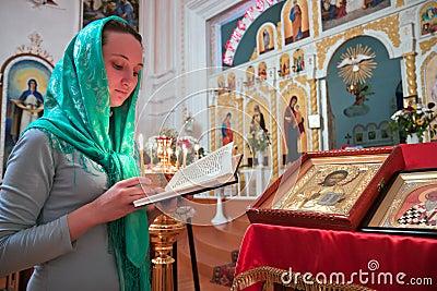 Een meisje leest een gebed in de kerk.
