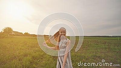 Een meisje met lang haar loopt op een verachtelijke manier rond het veld met haar lange haar stock video