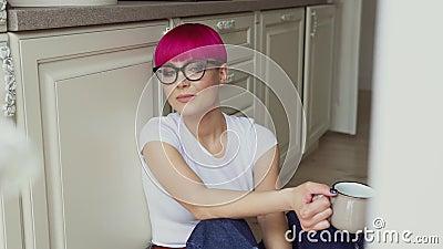 Een meisje zit op de vloer en drinkt thee stock videobeelden