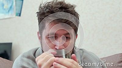 Een mens drinkt thee met citroen Hij heeft een koude, hoofdpijn, koorts, kou stock videobeelden