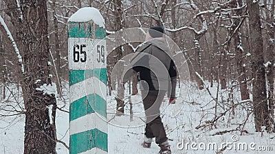 Een mens loopt naast een kwartpost in de de winter bosinspectie van bosbouw stock videobeelden