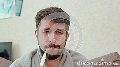 Een mens meet zijn temperatuur Hij heeft een koude, hoofdpijn, koorts, kou stock footage