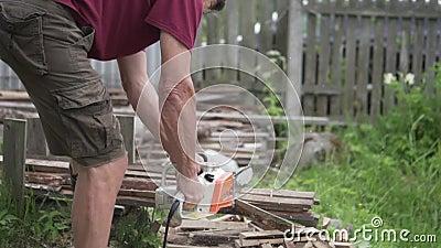Een mens zaagt hout met een elektrische zaag stock video