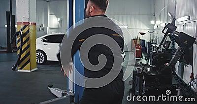 In een moderne auto-service is een knappe mannetjesmonteur in een uniform dansende blijdschap blij terwijl hij het repareren van  stock videobeelden