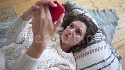 Een mooie vrouw in een witte trui doet een online aankoop met gezichts- en oogidentificatie, die op een deken ligt en stock video
