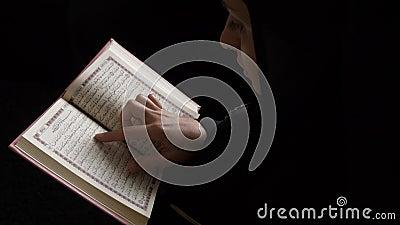 Een moslimvrouw in hijab houdt haar Koran vast en leest er een paar verzen uit stock video