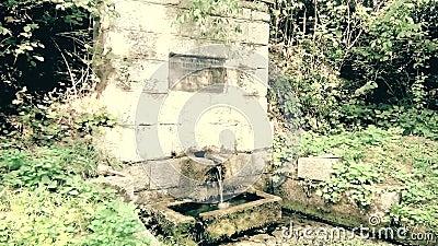 Een oude herdenkingsfontein met drinkbaar water in berg stock footage