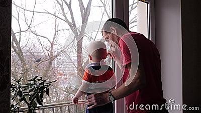 Een oude mens en zijn aanbiddelijke kleine kleinzoon spelen door het venster en de grootvader toont aan de babyjongen een vogel o stock footage