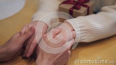 Een paar zit thuis aan tafel Een man houdt de handen van de vrouw vast en beroert ze. Cadeaudoos stock videobeelden