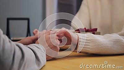 Een paar zit thuis aan tafel Een man houdt de handen van de vrouw vast en beroert ze. Cadeaudoos stock footage